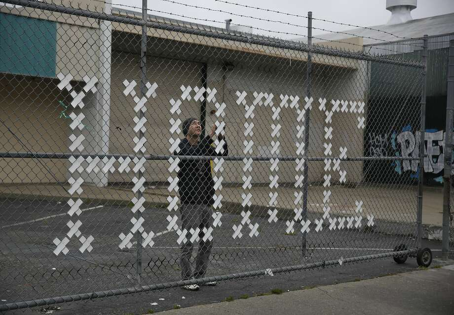 Artist Brian Singer touches up an art installation in San Fran cisco's Mission District to bring attention to homelessness. Photo: Lea Suzuki, The Chronicle