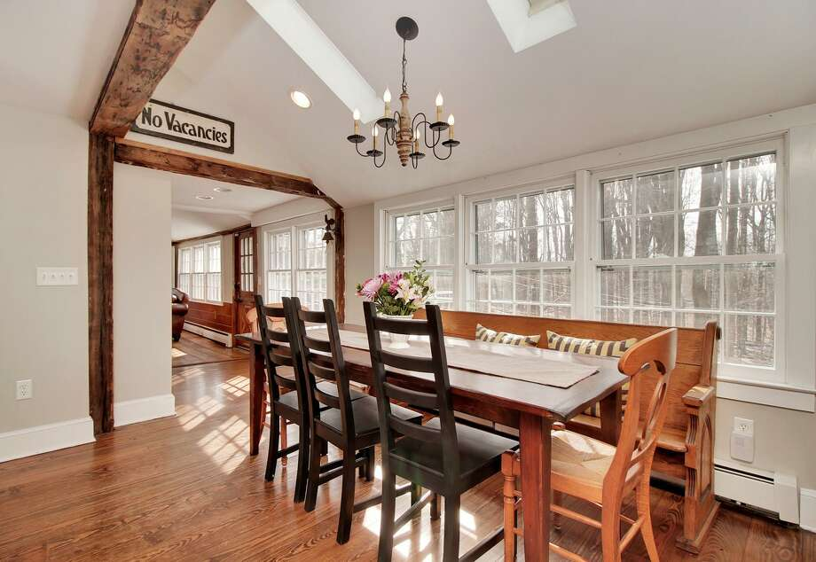 This New England saltbox at 58 Williams Road in Trumbull, Conn. mixes the antique and the modern. The 2,267 square foot-home dates back to circa 1770, but several renovations have been made, including a kitchen addition. The modern features are offset with rustic touches, such as original exposed brick fireplaces, hand-hewn beams and hardwood floors. Photo: Contributed Photo / Contributed Photo / Connecticut Post Contributed