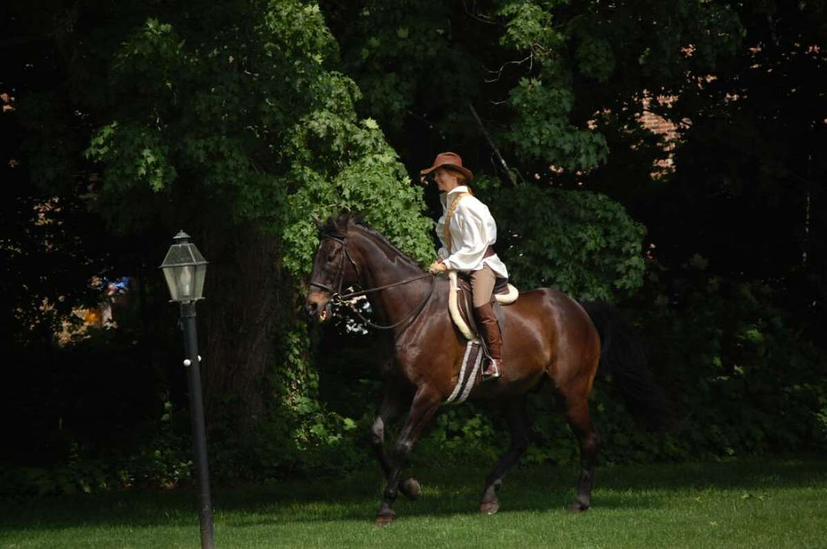 Ariane Mermod, portraying a courier in the 1800s, rides to the former home of Ebenezer Jesup to deliver a message: the town of Westport has officially been formed.