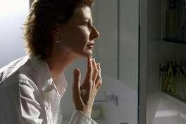 Woman inspecting skin in bathroom mirror