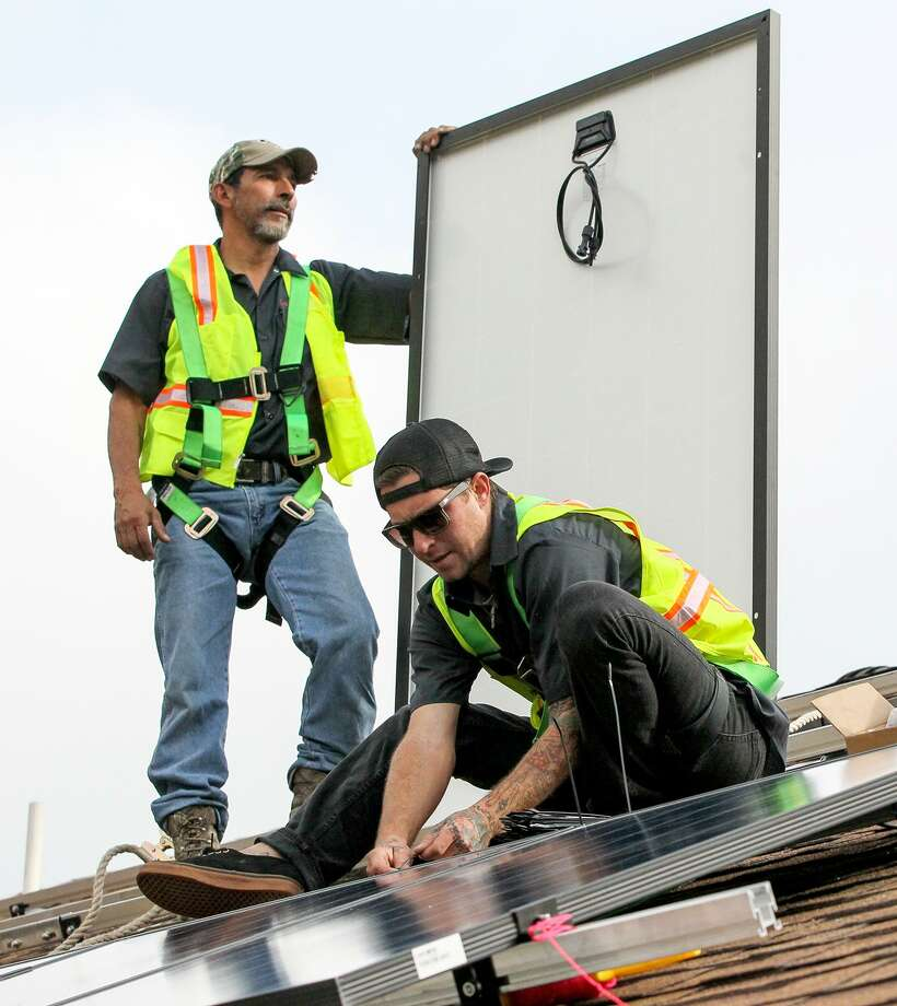 Solar workers install solar panels on a roof under CPS Energy's Solar Host SA program, which the utility conducted with PowerFin Partners. On Monday Canada-based Fengate Real Asset Investments announced it was purchasing PowerFin's San Antonio and Austin solar assets and providing $100 million in funding for the development of new solar projects in Texas. Photo: Marvin Pfeiffer /San Antonio Express-News / Express-News 2015