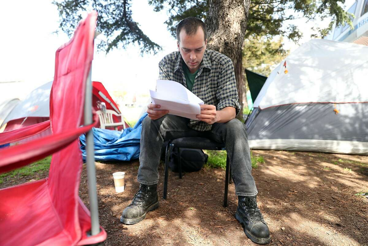 After receiving the press release from a fellow homeless person, Adam Bredenberg reads about Berkeley's Pathways Project at a homeless encampment on Martin Luther King, Jr. Way at Adeline Street in Berkeley, Calif., on Thursday, March 16, 2017.
