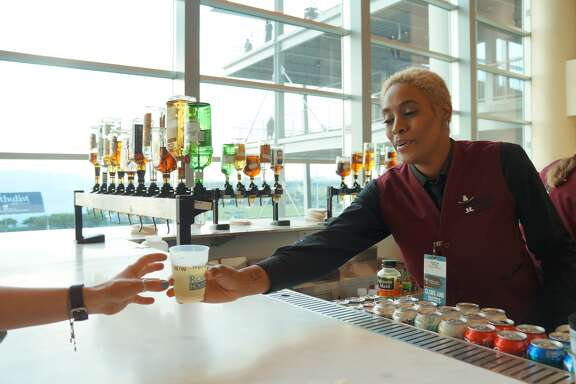 Angela Burrell serves a customer her drink at the NRG Stadium's West Club during the Houston rodeo. Burrell got her gig through the mobile app called, Shiftgig.