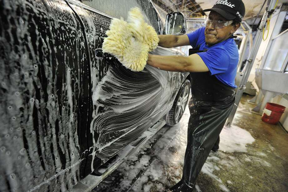 Julio Guaman scrubs down a car at Splash Car Wash in Greenwich, Conn., on Tuesday, Aug. 26, 2014. Splash Car Wash is among the companies that have been named a Top Workplace by Workplace Dynamics and Hearst Connecticut Media. Guaman has worked for Splash Car Wash for the past 20 years. Photo: Jason Rearick / Jason Rearick / Stamford Advocate
