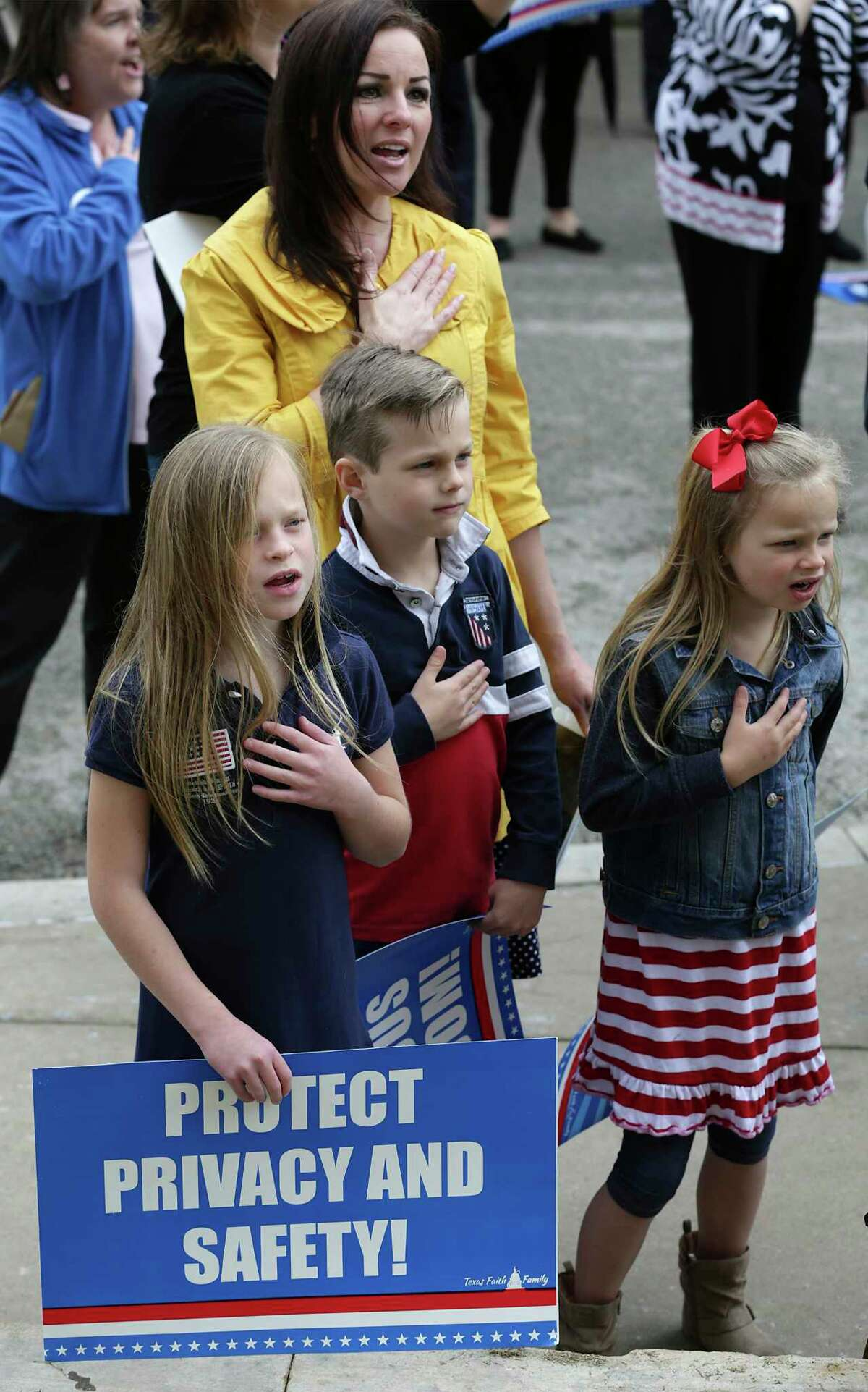 Nikki Kelton, above, and her kids Avary, 8, left to right, River, 7, and Ella Grace, 5, sing the National Anthem at the Faith and Family Rally at the State Capitol in Austin, TX on Thursday, March 16, 2017.