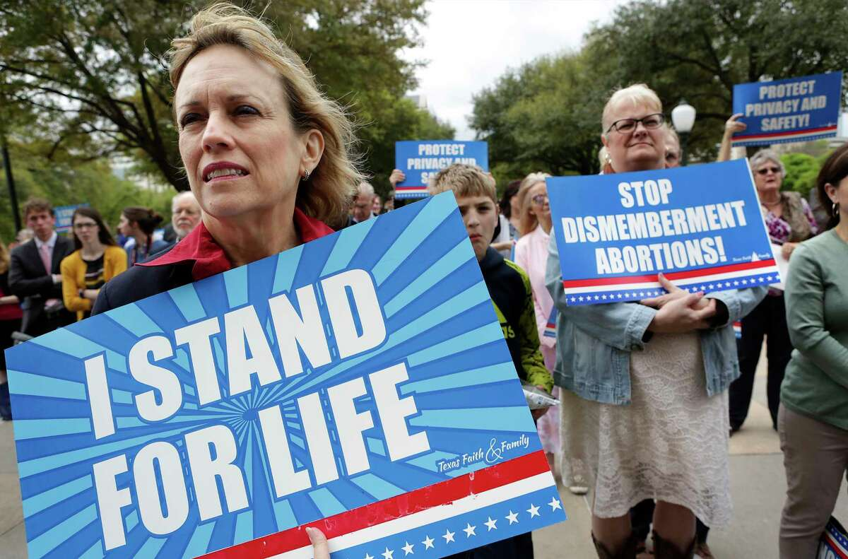 Dr. Linda Flower, left, of Tom Ball, TX holds a sign as she and others listen to Rev. Rafael Cruz, father of U.S. Sen. Ted Cruz at the Faith and Family Rally at the State Capitol in Austin, TX on Thursday, March 16, 2017.