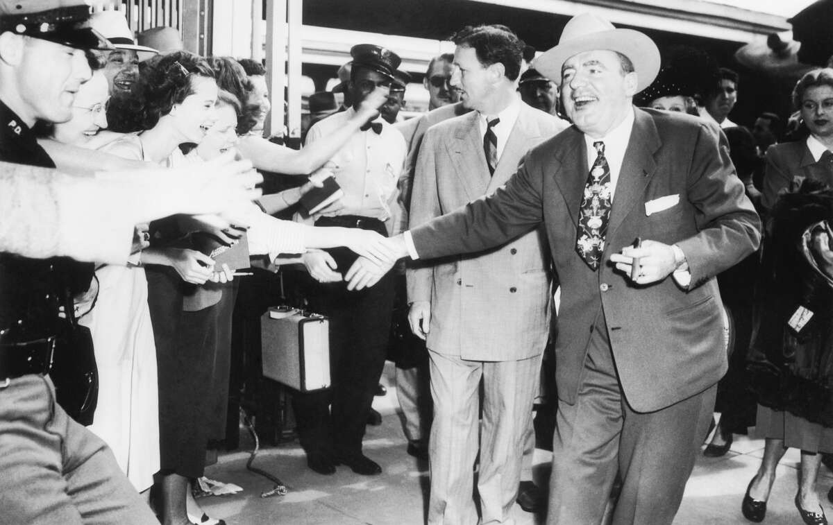 Pat O'Brien, movie star, right, and Glenn McCarthy, Houston oilman and owner of the Shamrock Hotel are greeted by fans on arrival of the