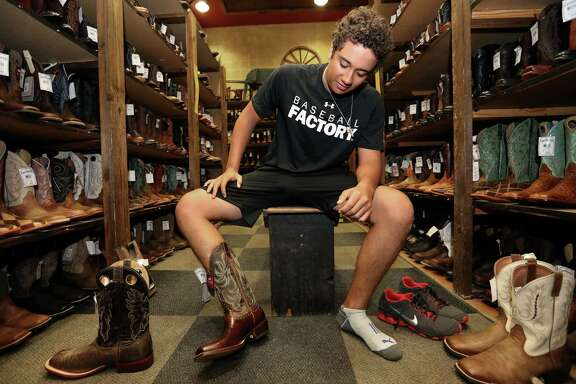 Diego Rivera, 18, tries on and compares different pairs of cowboy boots to find the right pair for his first pair of cowboy boots at Cavernder's before headed to Luke Bryant's concert at Houston Livestock Show and Rodeo with his girlfriend Thursday, March 16, 2017, in Houston. Rivera started with looking to buy a flannel shirt, but ended up getting the whole outfit.