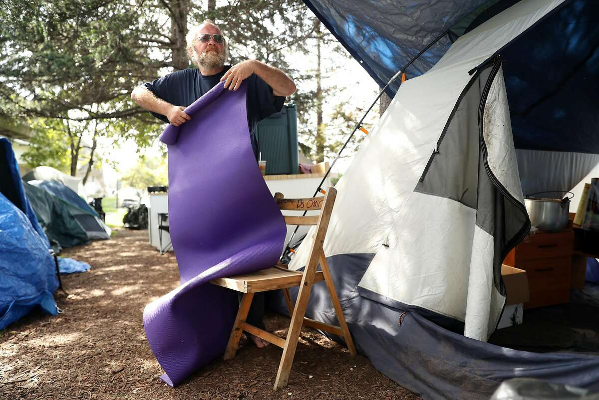 Brett Schnaper cleans up his campsite at a homeless encampment on Martin Luther King, Jr. Way at Adeline Street in Berkeley, Calif., on Thursday, March 16, 2017.