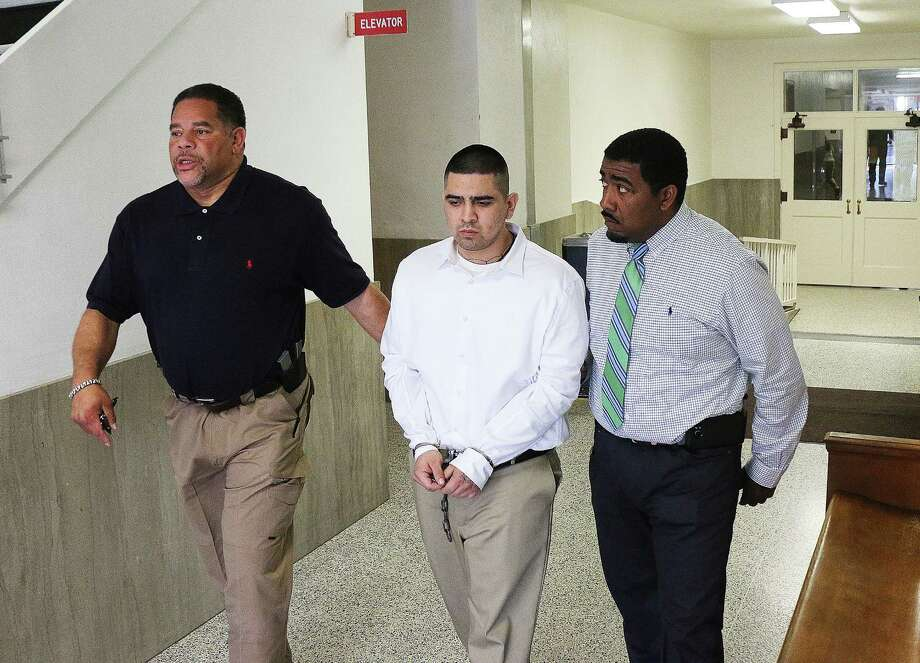 Roberto Ismael Alvarado Jr. is led away from the Liberty County Courthouse by Robert Harper and Chadwick Elmore, bailiffs for the 253rd State District Court. Alvarado was sentenced to 65 years in prison Wednesday for his part in the Dec. 16, 2015 murder of a convenience store clerk in Cleveland. Three other young men accused of participating in the crime have accepted plea agreements and are awaiting sentencing. Photo: David Taylor