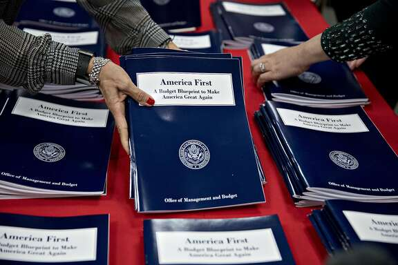 Employees arrange copies of U.S. President Donald Trump's fiscal 2018 budget request, America First: A Budget Blueprint to Make America Great Again, at the Government Printing Office (GPO) library in Washington, D.C., U.S., on Thursday, March 16, 2017. President Donald Trump is proposing historically deep budget cuts that would touch almost every federal agency and program and dramatically reorder government priorities to boost defense and security spending. Photographer: Andrew Harrer/Bloomberg