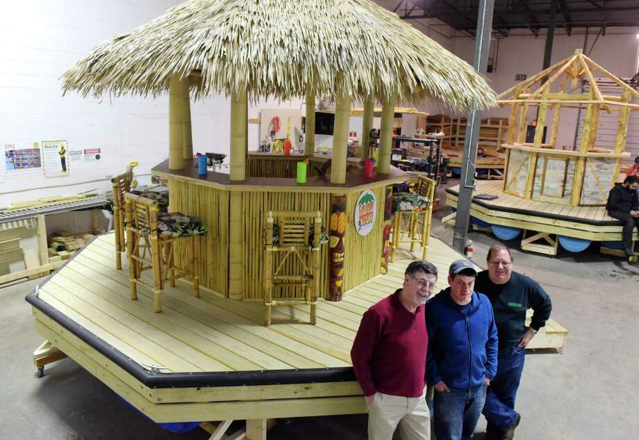 Bob Wolfgang, left, CEO of Cruisin Tikis, his son, Brian Wolfgang, center, COO of the company and Larry Davis, the founder and investor of the company, pose for a photo with one of their floating, powered tiki bars at the Cruisin Tikis manufacturing facility on Wednesday, March 15, 2017, in Colonie, N.Y.   (Paul Buckowski / Times Union) Photo: PAUL BUCKOWSKI / 20039966A