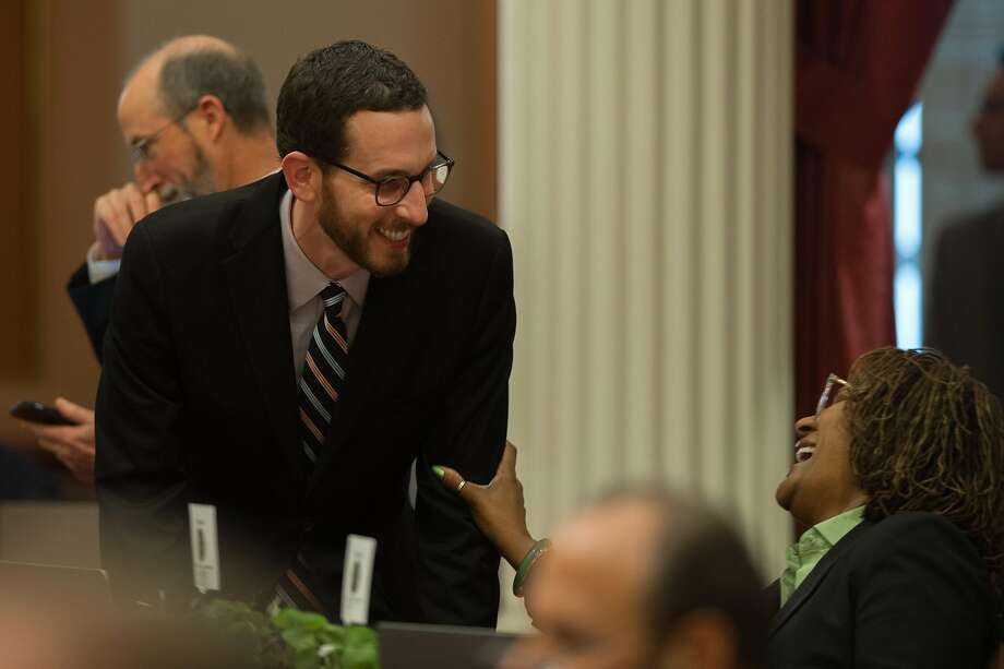 "Sen. Scott Wiener, D-San Francisco, left, talks with Sen. Holly Mitchell, D-Los Angeles, on the Senate floor in the state Capitol in Sacramento in March. Wiener is co-sponsoring a bill that would allow Californians to opt for a ""nonbinary"" gender marker on all forms of state identification. Photo: Chris Kaufman, Special To The Chronicle"