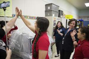 Gaby Garcia, center left, and Ashley Cash, counselor, center right, give high fives to the Young Women's Leadership Academy robot team in 2017. SAISD officials announced Wednesday the district will open an all-girls elementary school next year to provide a pipeline of new students to the academy.