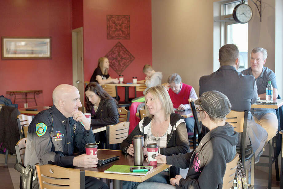 BRITTNEY LOHMILLER   blohmiller@mdn.net Midland residents Gwen Malone, center, and Stephanie Thomas, right, chat with Midland Police Chief Clifford Block at Coffee Chaos Thursday morning during the first Coffee with a Cop. / Midland Daily News