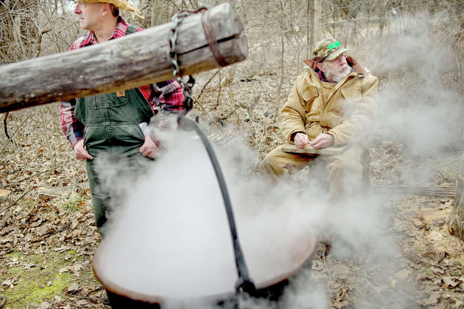 FILE — Bill Ferris, right, whittles maple spiles out of wood as he and Phillp Meister, left, watch over a kettle of syrup cooking over an open fire during last year's Maple Syrup Day at the Chippewa Nature Center. / Midland Daily News