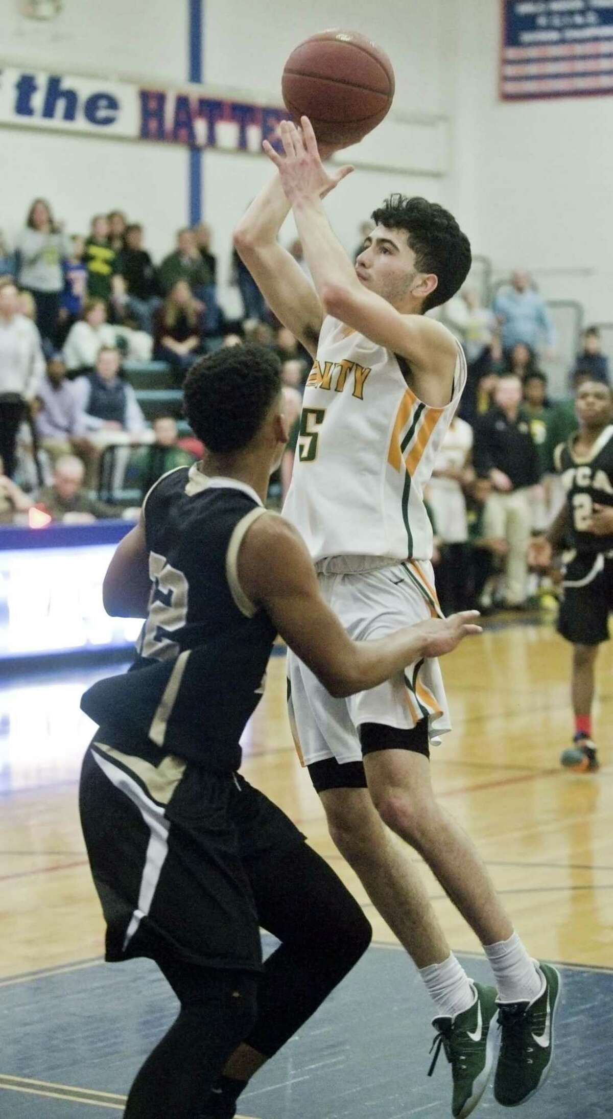 Trinity Catholic High School's Peter Galgano stretches for the shot during the semifinals against Waterbury Career Academy, played at Danbury High School. Thursday, March 16, 2017