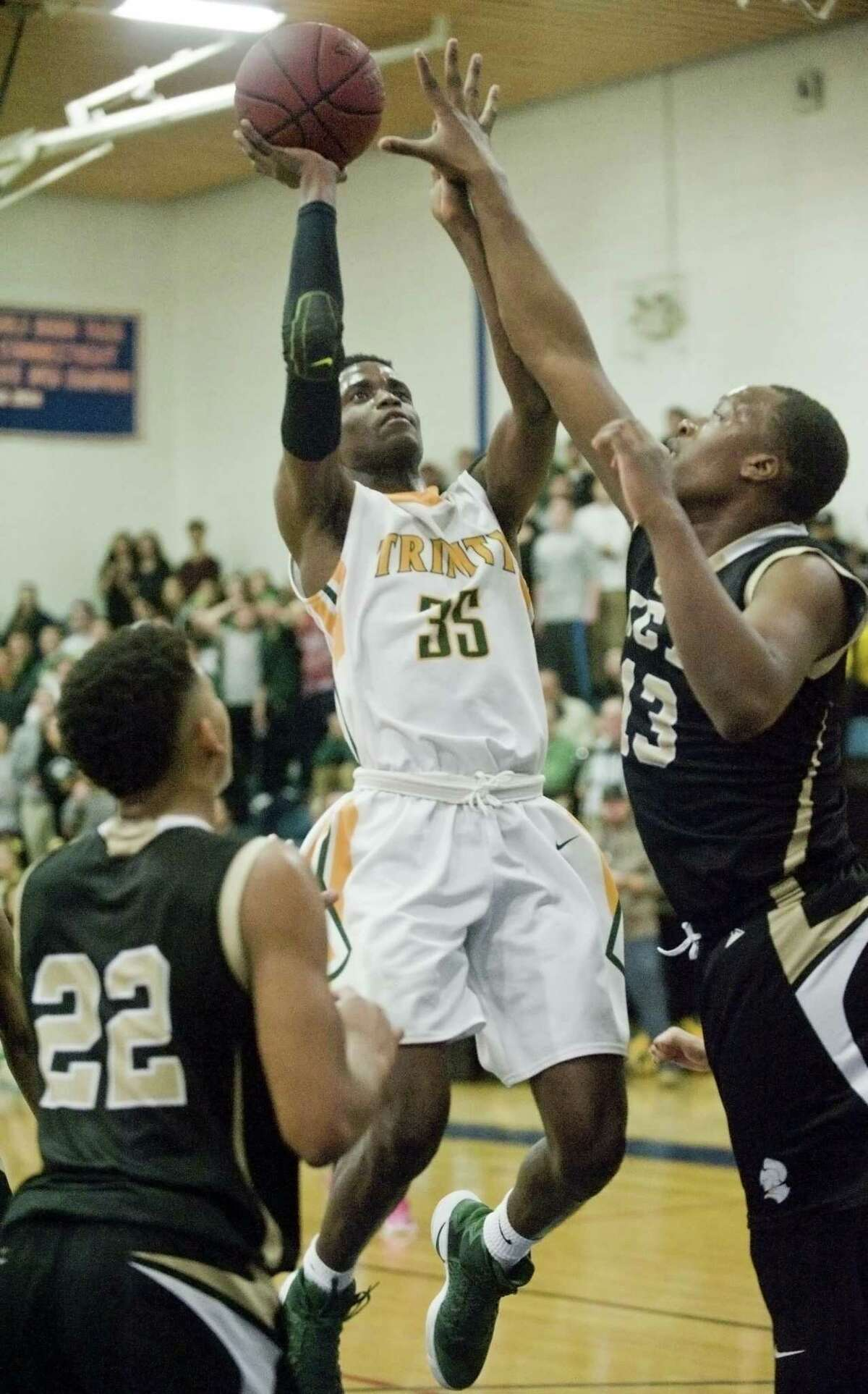 Trinity Catholic High School's Dimitry Moise goes up for the shot as Waterbury Career Academy's Chad McKoy defends during the semifinals played at Danbury High School. Thursday, March 16, 2017