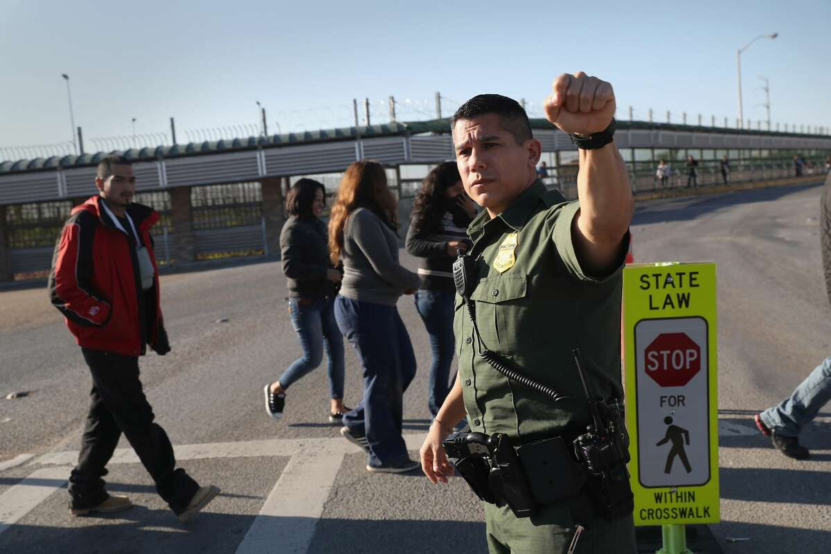 GALLERY:U.S.-Mexico border through the decades HIDALGO, TX - MARCH 14: A U.S. Border Patrol agent stops traffic as immigrants are deported across an international bridge into Mexico on March 14, 2017 from Hidalgo, Texas. The Trump administration has ordered an increase in deportations, part of the larger strategy to get tough on illegal immigration and strengthen border security. The U.S. Border Patrol has reported that illegal crossings from Mexico have dropped some 40 percent along the southwest border since Trump took office. (Photo by John Moore/Getty Images)