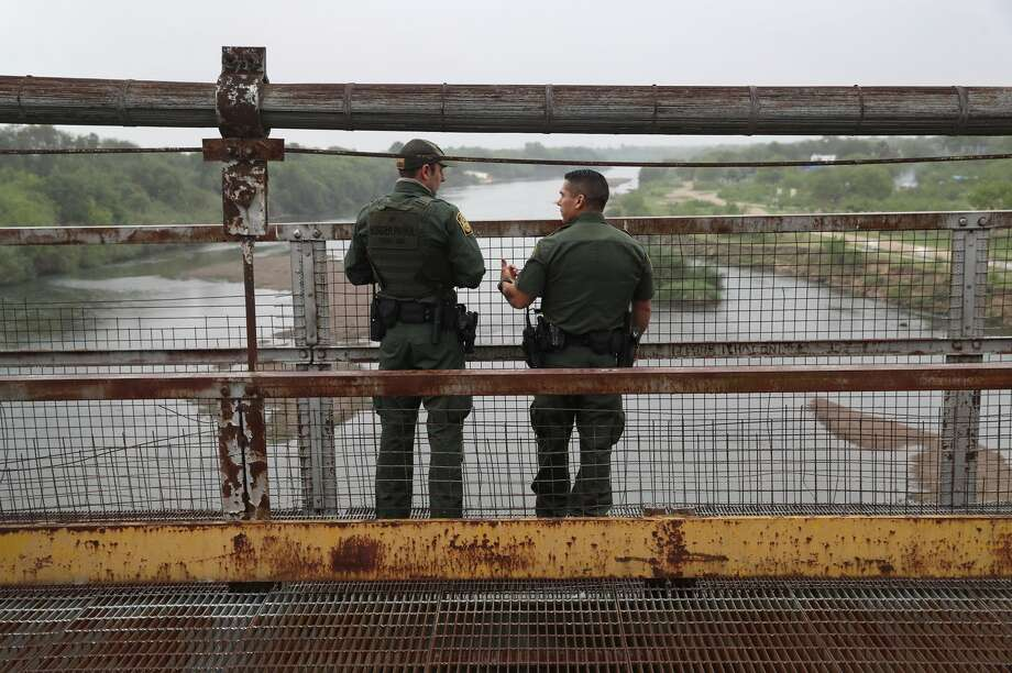 U.S. Border Patrol agents talk while on a bridge over the Rio Grande at the U.S.-Mexico border. Photo: John Moore/Getty Images