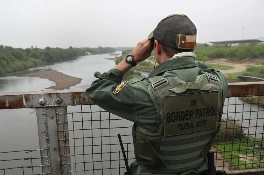 A U.S. Border Patrol agent scans the U.S.-Mexico border while on a bridge over the Rio Grande on March 13, 2017 in Roma, Texas. The Border Patrol has reported that illegal crossings from Mexico have dropped some 40 percent along the southwest border since Donald Trump took office.  (Photo by John Moore/Getty Images) Photo: John Moore/Getty Images