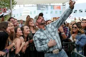 Country legend Garth Brooks takes selfies with fans at RodeoHouston Thursday after  announcing he will return to the stage after a 25-year hiatus.