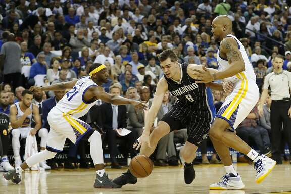 Mario Hezonja (8) of the Orlando Magic drives towards the basket as he is being defended by Ian Clark (21) and David West (3) of the Golden State Warriors during the fourth quarter of their NBA basketball game at Oracle Arena in Oakland, Calif. on Thursday, March 16, 2017. The Warriors defeated the Magic 122-92.