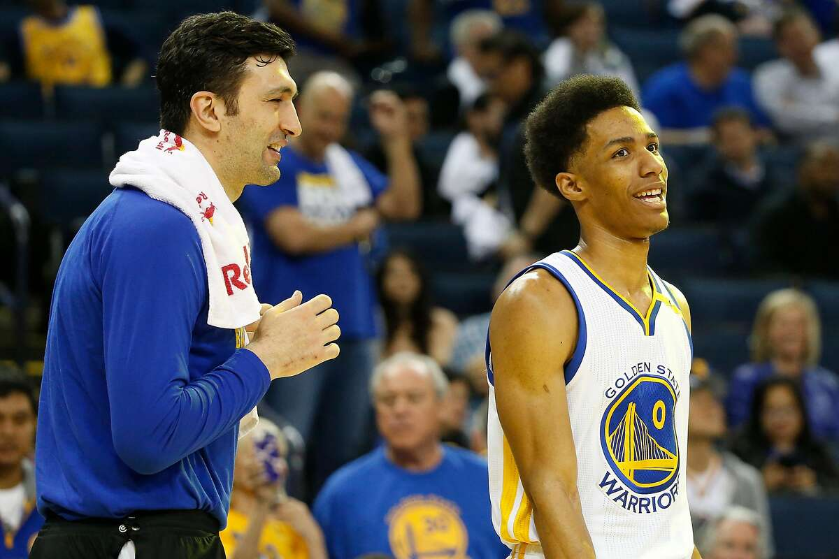 Zaza Pachulia (27), left, shares a laugh with teammate Patrick McCaw (0) of the Golden State Warriors during the fourth quarter of their NBA basketball game against the Orlando Magic at Oracle Arena in Oakland, Calif. on Thursday, March 16, 2017. The Warriors defeated the Magic 122-92.