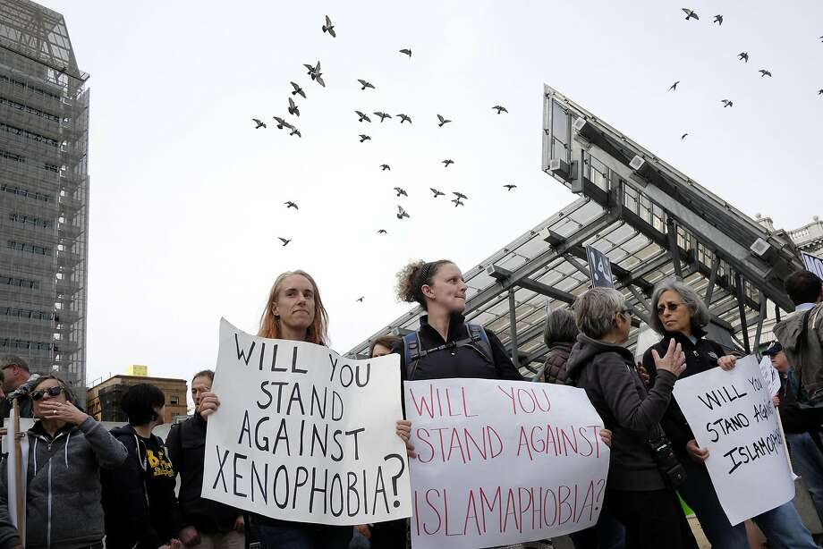 FILE -- Melissa Kachura, left, and Rachelle Burnaford hold signs during a protest against President Trump's new travel ban in front of the Federal Building in San Francisco, CA, on Thursday March 16, 2017. A GenForward poll found that the majority of young adults — 57 percent — see Trump's presidency as illegitimate, including about three-quarters of blacks and large majorities of Latinos and Asians.Keep clicking to see a detailed view of President Trump's first 100 days in office. Photo: Michael Short, Special To The Chronicle