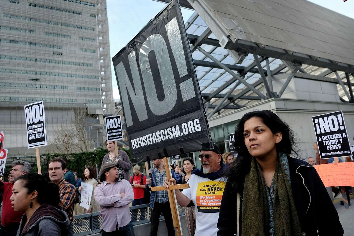 Asian Law Caucus staff attorney Christina Sinha listens to speakers during a protest against President Trump's new travel ban in front of the Federal Building in San Francisco, CA, on Thursday March 16, 2017.