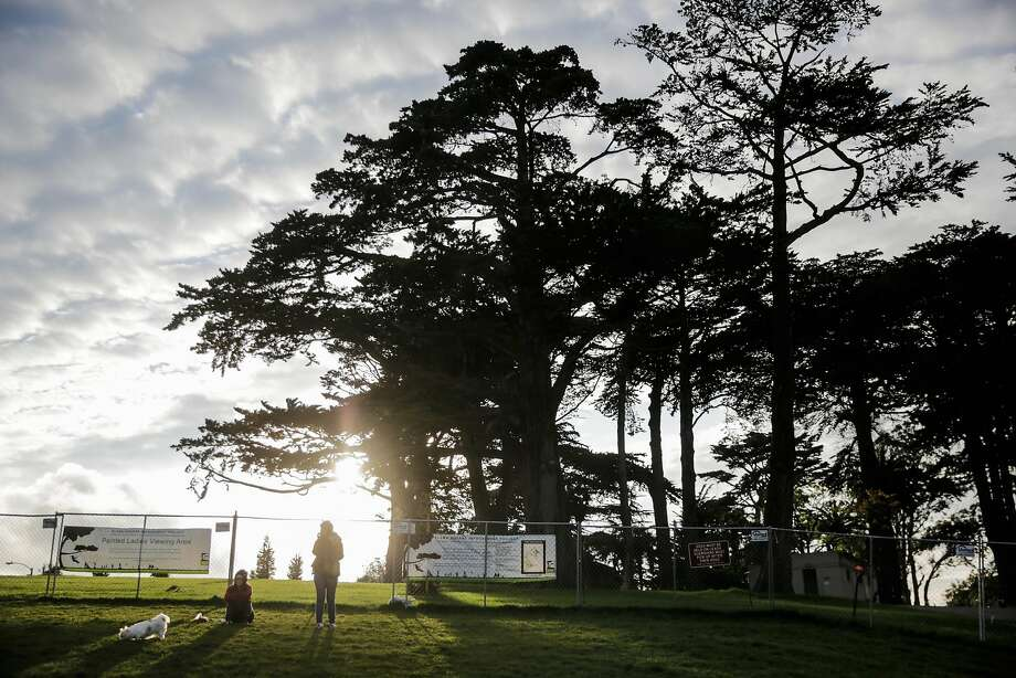People relax outside a fence at Alamo Square Park, which is awaiting park work that was expected to take seven months but could take more than a year. Photo: Gabrielle Lurie, The Chronicle