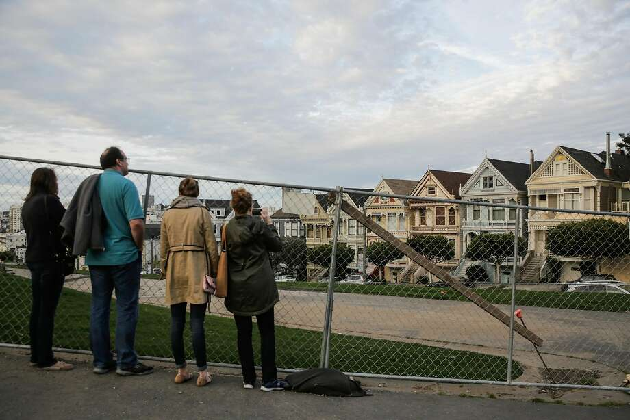 Tourists Katie (left), Rob, Leah and Karen Johnson, who are visiting from Austin, Texas, look at the Painted Ladies through fencing that is blocking off Alamo Square Park while it waits for new sod and other renovations. Photo: Gabrielle Lurie, The Chronicle