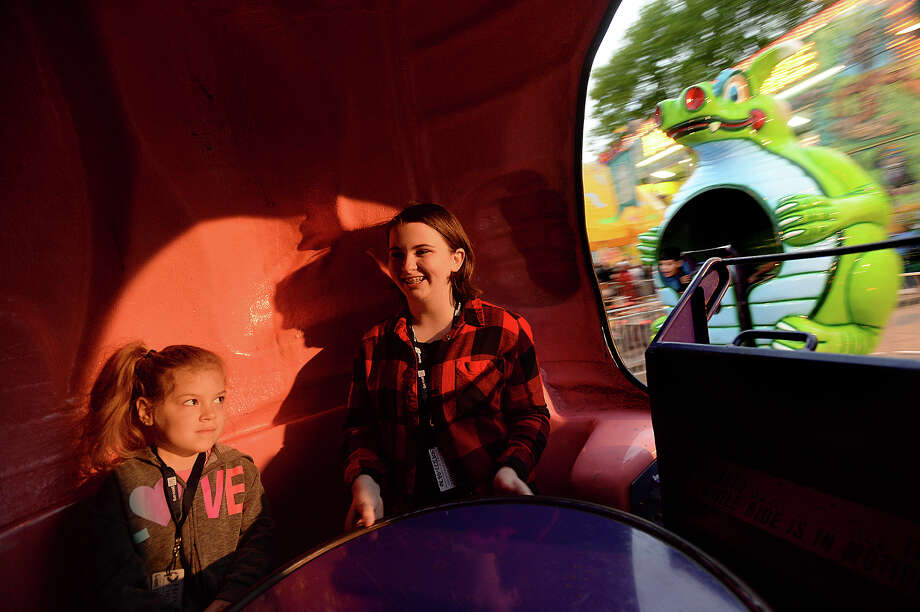 Alivia McClain and younger sister Lillian Bauhan enjoy spinning inside their giant dragon as they and family enjoy the carnival rides at this year's annual Nederland Heritage Festival. The event continues through Sunday and will feature a parade 10 a.m. Saturday, as well as a chili cook-off. Photo taken Thursday, March 16, 2017 Kim Brent/The Enterprise Photo: Kim Brent / BEN