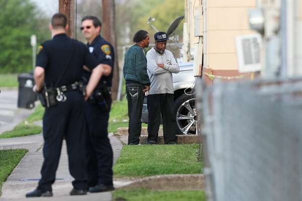 Two men stand near Houston police as they investigate the scene where a body was found in the 4600 block of Market Street, Friday, March 17, 2017, in Houston.