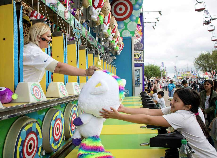 Claire Condon, left, from Cape Town, South Africa, hands a stuffed unicorn to Abigail Medrano, 9, right, after she won  the prize at the Houston Livestock Show and Rodeo, Thursday, March 16, 2017, in Houston. Condon is one of 285 carnival workers at the rodeo who are H2B visa holders. Photo: Jon Shapley, Houston Chronicle / © 2017 Houston Chronicle