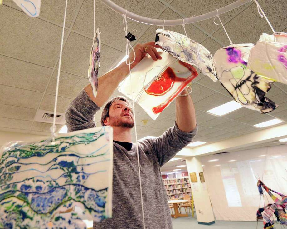 Art teacher Michael Manning installs a stained-glass artwork done by his North Mianus School students that was on display as part of the Greenwich Public Schools K-12 District Art Show at the media center in Greenwich High School, Conn., Thursday, March 16, 2017. The show runs until March 29th and features artwork from students in all the Greenwich Public Schools. Photo: Bob Luckey Jr. / Hearst Connecticut Media / Greenwich Time