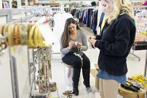Employees Helen Iafrate, left, and Marissa Goetz, right, hang jewelry on Friday at the new Merchandise Outlet off M-20. The store will open Wednesday at 9.m. Hours are Monday through Saturday 9 a.m to 7 p.m. and Sunday 10 a.m. to 5 p.m. Owner Mike Schuette owns nine other stores in northern Michigan and has been eyeing this store space for years.