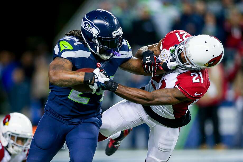 Seahawks running back Marshawn Lynch stiff arms Arizona's Patrick Peterson after a 10-yard gain in the first quarter of the Seattle Seahawks-Arizona Cardinals game at CenturyLink Field in Seattle on Sunday November 15, 2015. (Photography by Scott Eklund/Red Box Pictures) Photo: Scott Eklund, Red Box Pictures