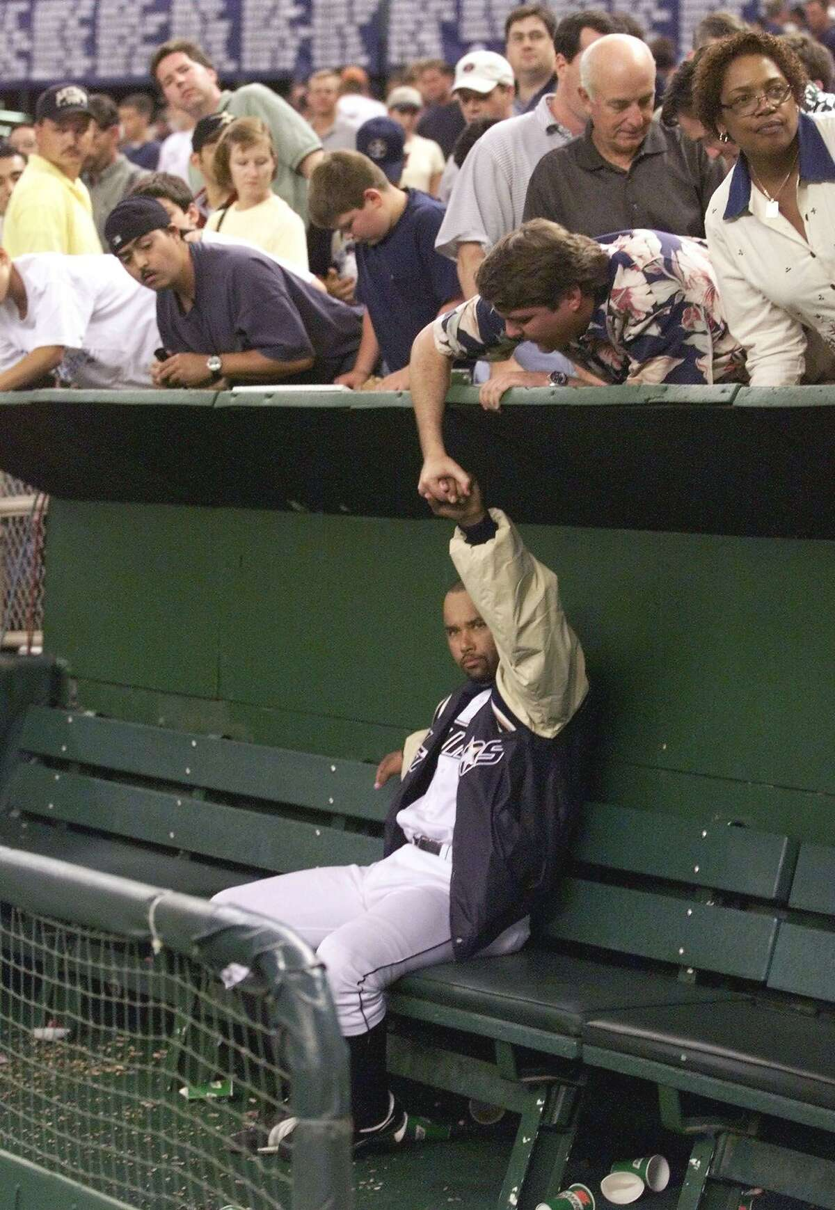 A fan reaches over the dugout to shake hands with pitcher Jose Lima of the Houston Astros after game four of the National League Divisional Series October 9, 1999 at the Astrodome. The Braves won the game 7-5 to win the best-of-five game series 3-1 to advance to the NLCS against the New York Mets.