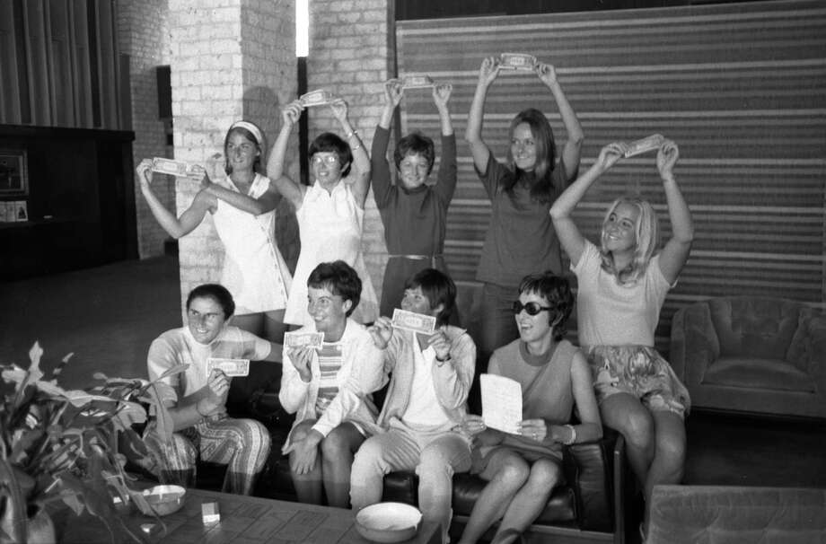 Top female tennis players hold up the $1 bills which made them eligible to play for money in the Virginia Slims tournament at the Houston Racquet Club. Photo: Bela Ugrin, HP Staff / Houston Chronicle