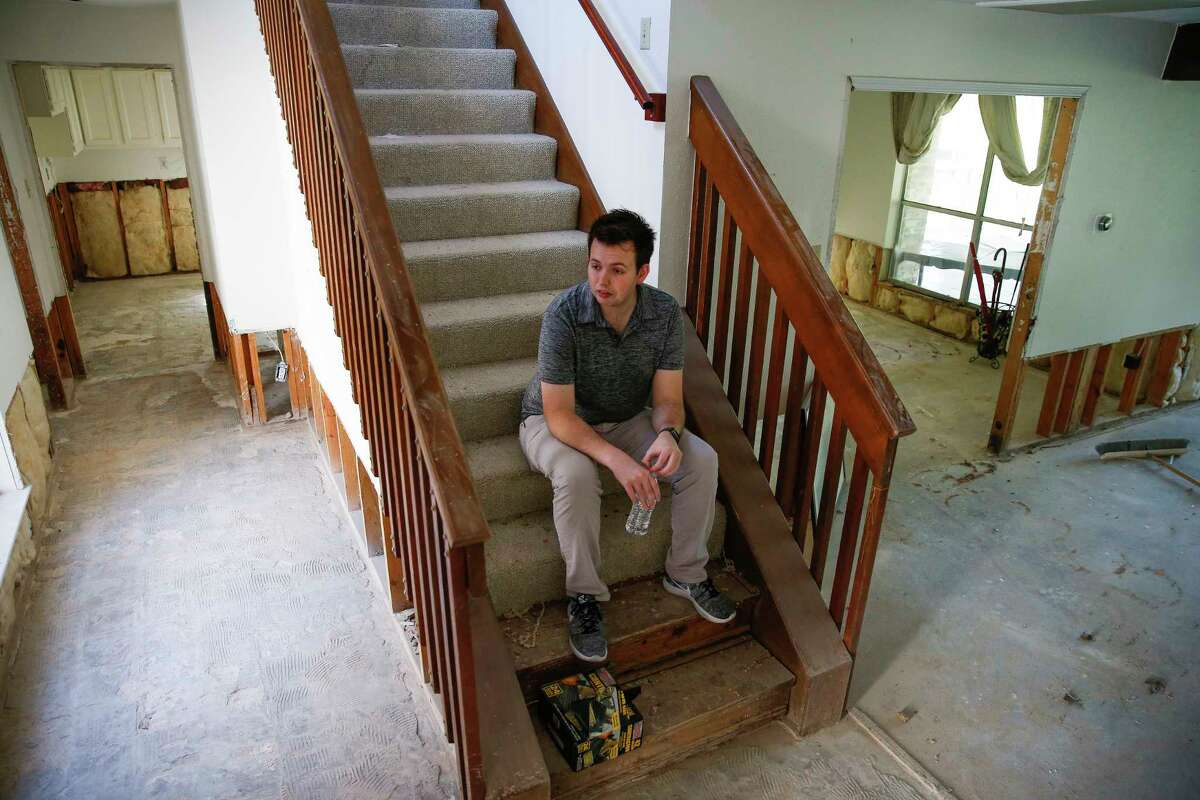 Christian Rumscheidt sits on the stairs in his house Wednesday, March 8, 2017, which is still undergoing repairs after it was flooded last April. ( Michael Ciaglo / Houston Chronicle )