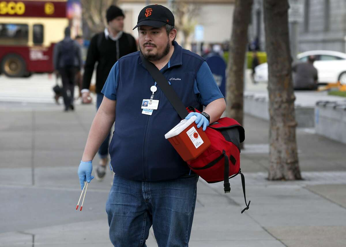 Armed with tongs and a secure container, Jose Luis Guzman, from the Department of Public Health, looks for discarded hypodermic needles near the main branch of the public library in San Francisco, Calif. on Thursday, March 16, 2017.