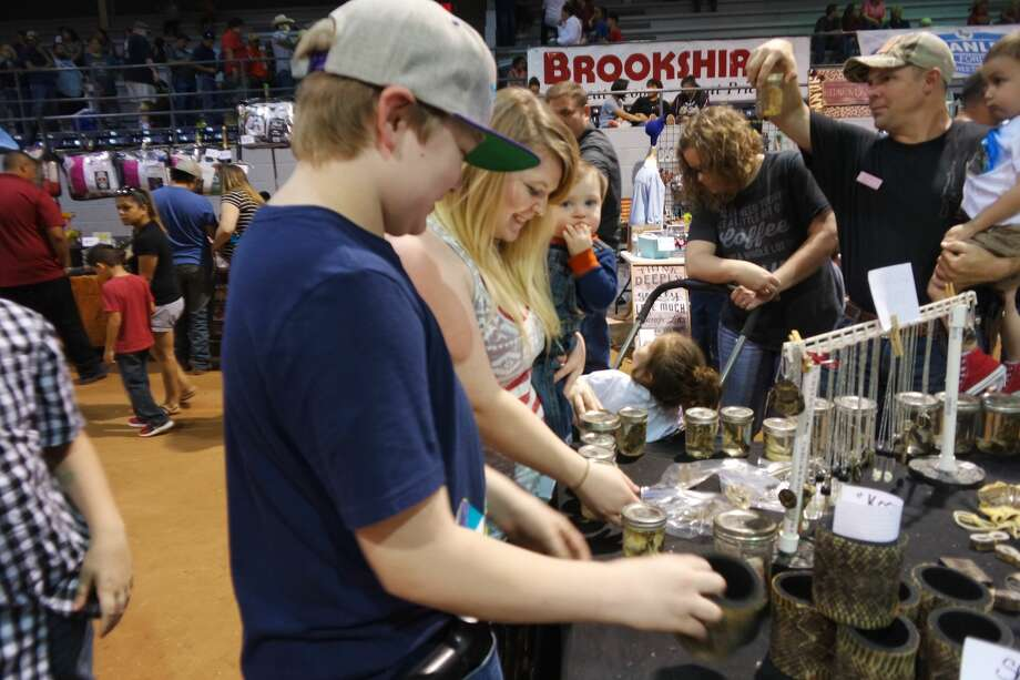 Dean Key, left, Brooke Ingram and Bentley Chatham, relatives from the Abilene area, shop for items at the Reptiles Unlimited booth at the Rattlesnake Roundup on March 11. Photo: Simone Jasper/Reporter-Telegram