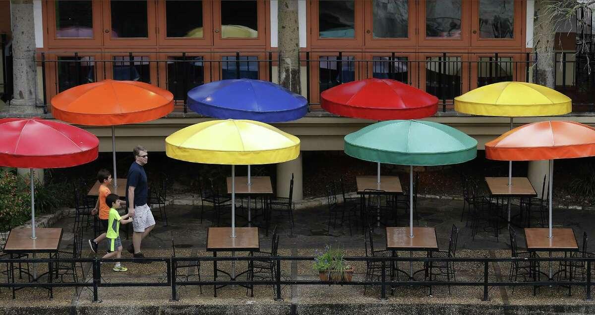 A family walks past a series of umbrellas by Casa Rio Restaurant on the River Walk on Thursday, Mar. 16, 2017. (Kin Man Hui/San Antonio Express-News)