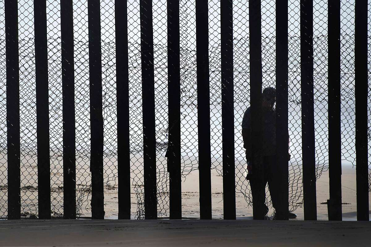 (FILES) This file photo taken on February 13, 2017 shows a man standing on the Mexico side of a border fence separating the beaches at Border Field State Park, in San Diego, CA. Some Hispanic business owners in the United States are offering to help build President Donald Trump's wall to keep out unauthorized immigrants on the Mexican border, despite controversy and their personal misgivings.