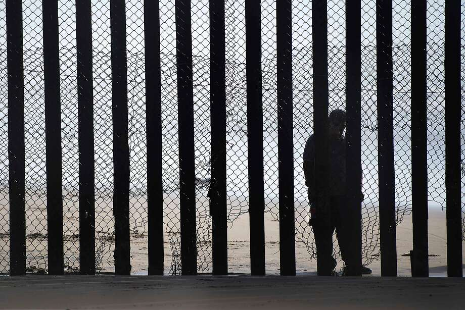 A man stands on the Mexico side of a border fence that separates the Tijuana River estuary beaches at Border Field State Park in San Diego. Photo: JIM WATSON, AFP/Getty Images