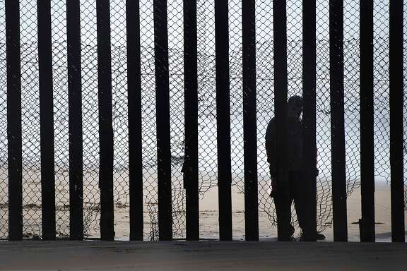 "(FILES) This file photo taken on February 13, 2017 shows  a man standing on the Mexico side of a border fence separating the beaches at Border Field State Park, in San Diego, CA.  Some Hispanic business owners in the United States are offering to help build President Donald Trump's wall to keep out unauthorized immigrants on the Mexican border, despite controversy and their personal misgivings.""Myself, being an Hispanic makes it tougher,"" Michael Luera, who runs a construction services firm in Ganado, Texas, told AFP.His company, Fairfield Logistics, recently expressed interest in working on the border wall project, which has become a lightning rod for public outrage in the debate over Trump's immigration policies. But it was not an easy choice.   / AFP PHOTO / JIM WATSONJIM WATSON/AFP/Getty Images"