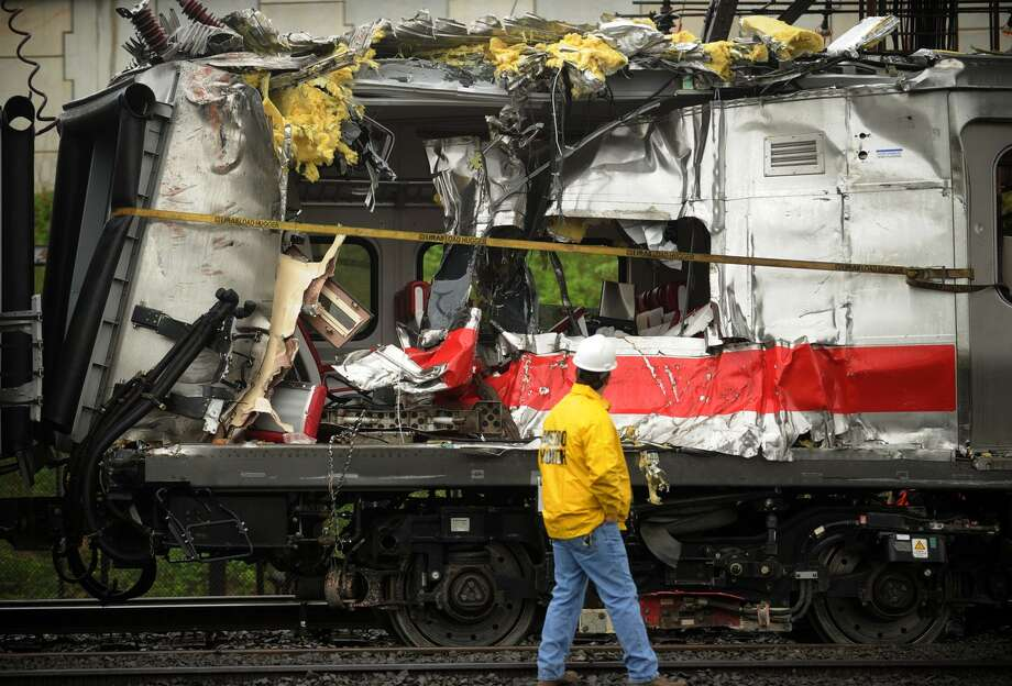 Metro North train cars heavily damaged the derailment are pulled from the scene after being hoisted back on to the tracks in Bridgeport. Conn. May 19, 2013. Photo: Brian A. Pounds / File Photo / Connecticut Post