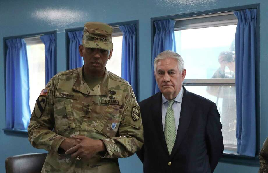 U.S. Secretary of State Rex Tillerson, right, is briefed by U.S. Gen. Vincent K. Brooks, commander of the United Nations Command, Combined Forces Command and United States Forces Korea as a North Korean soldier, rear right, takes a photograph through a window at the U.N. Command Military Armistice Commission meeting room at the border village of Panmunjom, which has separated the two Koreas since the Korean War, South Korea, Friday, March 17, 2017. Photo: Lee Jin-man, AP / AP POOL