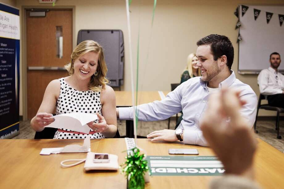 Fourth-year Michigan State University College of Human Medicine student Rachel Rezmer, left, and husband Adam Rezmer, right, smile while learning that Rachel has placed at St. Joseph Mercy Ann Arbor for a residency program in obstetrics and gynecology during Match Day at the MidMichigan Medical Center Gerstacker Building on Friday. Ten students opened envelopes to find out where they had been matched for a residency program whether in Michigan or across the country. Photo: Erin Kirkland/Midland Daily News